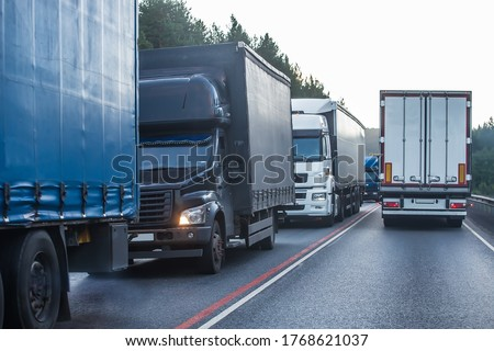 Trucks in a traffic jam on a suburban highway. Delayed delivery of goods. Royalty-Free Stock Photo #1768621037