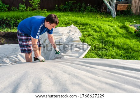 A man covers a dug hole with geotextile. Garden work, do-it-yourself pool Royalty-Free Stock Photo #1768627229