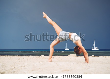 Yoga on the beach. Woman practicing yoga on coastline of the ocean. Beautiful girl relaxing by the sea. Calm, serene, minimalist photo with copy space. Healthy active lifestyle, vitality, zen. #1768640384