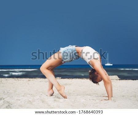 Yoga on the beach. Woman practicing yoga on coastline of the ocean. Beautiful girl relaxing by the sea. Calm, serene, minimalist photo with copy space. Healthy active lifestyle, vitality, zen. #1768640393