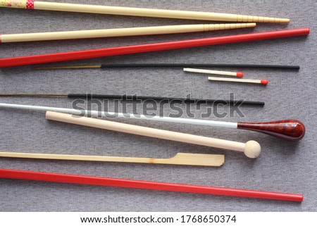 Assortment of sticks lined horizontally on grey fabric background including Japanese and Chinese chopsticks, aromatic incense, matches, conductor's baton, wooden pencil and bamboo skewer #1768650374