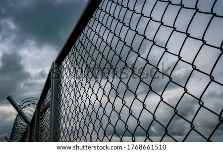 Military zone mesh fence. Prison security fence. Looking up view of barbed wire security fence with storm sky and dark clouds. Razor wire jail fence. Barrier border. Boundary security wall.  #1768661510