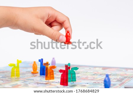 Child play a board game. Child's hand holds a figure for the game #1768684829