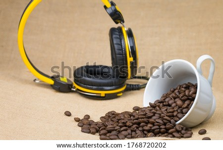 Roasted coffee beans In a white coffee cup on its side and a lot of coffee beans scattered on the floor and music headphones placed behind the picture and the bottom surface is a brown fabric.