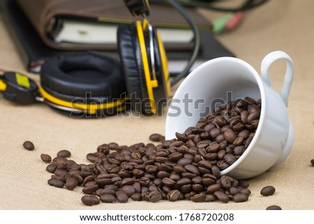 Roasted coffee beans In a white cup of coffee on its side and a lot of coffee on the ground and a notebook and music headphones Placed behind the picture and the bottom surface is a brown fabric