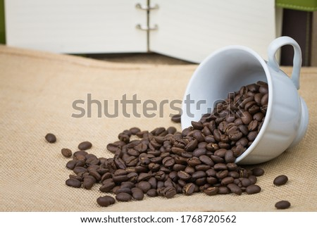 Roasted coffee beans In a white cup of coffee on its side and a lot of coffee beans scattered on the floor and a blank notebook Placed behind the picture and the bottom surface is a brown fabric