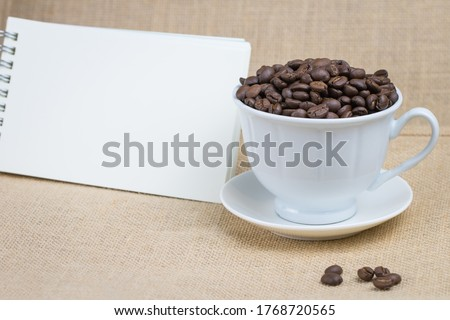 Roasted coffee beans In a white coffee cup and with a blank notebook and the bottom surface is a brown fabric and a few coffee beans scattered on the floor and the picture has a blank space