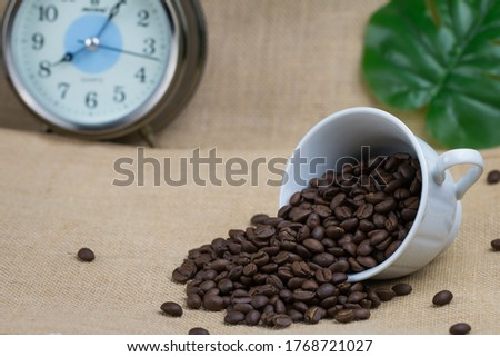 Roasted coffee beans In a white coffee cup on its side and a lot of coffee beans spread on the floor and an alarm clock placed behind the picture and the bottom surface is a brown fabric.