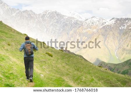 Tourist walks towards  orthodox Gergeti trinity church with green nature around. Trave to religious places and hiking around Akzbegi national park. Georgia.