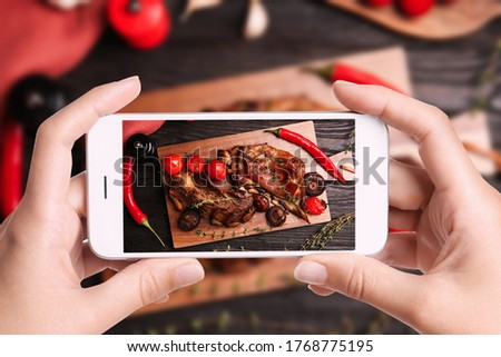 Blogger taking picture of delicious roasted ribs at table, closeup. Food photography