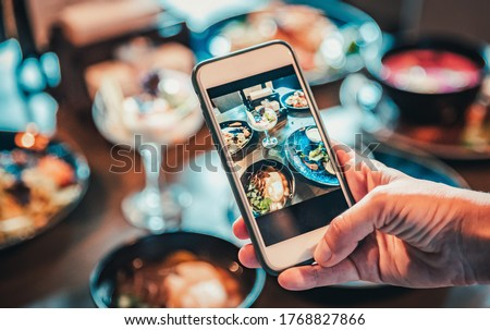 woman hand with smartphone photographing food at restaurant or cafe Royalty-Free Stock Photo #1768827866