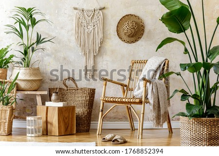Stylish and floral composition of living room interior with rattan armchair, a lot of tropical plants in design pots, decoration, macrame and elegant personal accessories in cozy home decor. Royalty-Free Stock Photo #1768852394