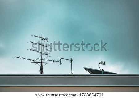 TV Antenna and Satellite dish with Blue Sky Background. Television antenna and satellite antenna on the roof. The old technology before Digital era. Royalty-Free Stock Photo #1768854701