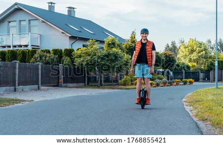 Young Man Riding On Electric Unicycle (EUC) On Street, Best Mobile Portable Personal Transportation Vehicle, Summer Day #1768855421