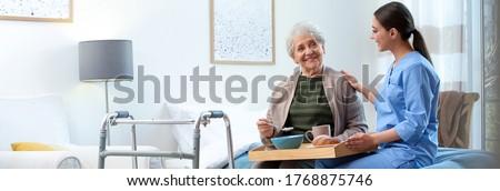 Care worker serving dinner for elderly woman on geriatric hospice. Banner design
