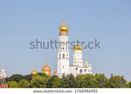 View of Ivan the Great Bell Tower above green trees on a summer morning in Moscow, Russia. It's a church tower inside the Moscow Kremlin complex. Clear blue sky. Theme of travel in Russia. #1768986905