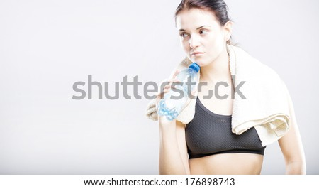 Tired natural woman after fitness class with water bottle and towel #176898743
