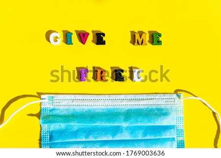 Coronavirus, self-isolation, medicine and health concept - flatlay of blue medical protective mask with appeal inscription give me free in multi-colored letter on bright yellow plain background.