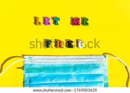 Coronavirus, self-isolation, medicine and health concept - flatlay of blue medical protective mask with appeal inscription let me free in multi-colored letter on bright yellow plain background.