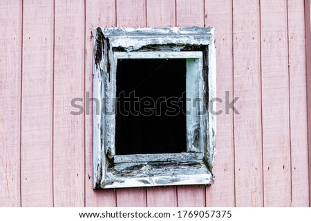 An open window framed with dirty old white painted wood with no glass. Dark interior with no lights and pink wooden plank siding of a barn, shed or house. No lights but black inside during sunny day