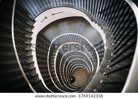 looking deep into long spiral stair case of big building, concept photo of architecture #1769142338