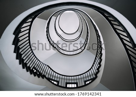 looking deep into long spiral stair case of big building, concept photo of architecture #1769142341