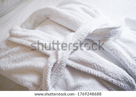 The concept of rest in a hotel. White terry bathrobe on bed in bedroom close-up.  Royalty-Free Stock Photo #1769248688
