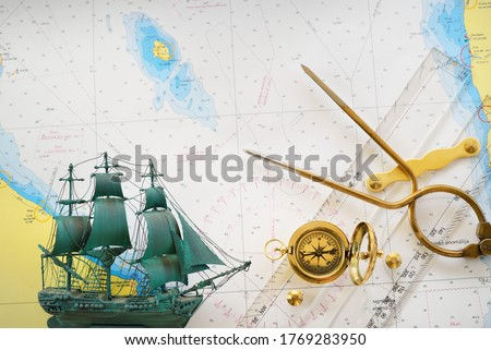 """Golden sundial, antique W & HC 6"""" brass dividers calipers nautical navigation chart tool, parallel ruler, tall ship scale model, old white map close-up. Vintage still life. Sailing, travel accessories Royalty-Free Stock Photo #1769283950"""