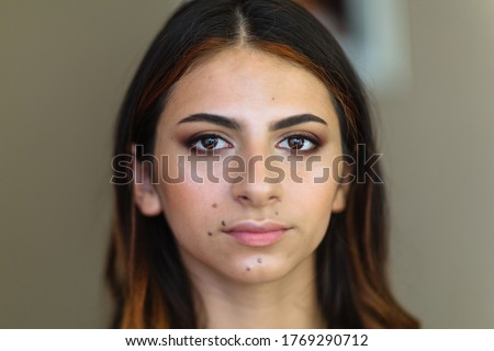Beautiful model in make up process. Portrait of young pretty woman with beutiful makeup in beauty studio salon. Evening make up, blurry background