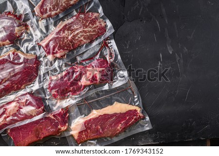 Vacuum packed organic raw beef alternative cuts: top blade, rump, picanha, chuck roll steaks, over black textured background, top view space for text. Royalty-Free Stock Photo #1769343152