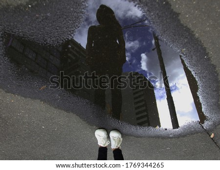 Reflection of girl wearing white shoes in water puddle on gloomy day #1769344265