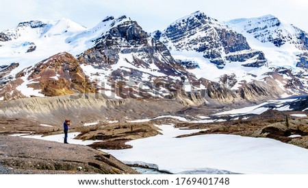 Photographer taking a picture of the Athabasca Glacier with Mount Andromeda, Mount Athabasca and Hilda Peak of the Columbia Icefields in Jasper National Park, Alberta, Canada in the background