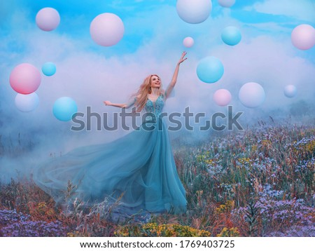 happy young beautiful blonde woman raised hand. Fantasy princess jumping touches pink ball air balloon. long blue tulle dress fluttering fly in wind. white clouds, fog, smoke colorful flowers meadow Royalty-Free Stock Photo #1769403725