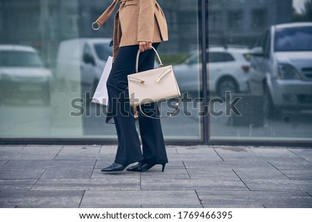 Cropped photo of a slim elegant Caucasian woman with shopping bags walking along the street