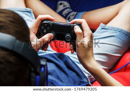Game joystick in the hands of a teenager close-up. Teenage boy in big headphones sits with a joystick at home, top view. The guy is sitting on a red bean bag chair. Computer games. Play online.