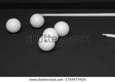 Billiard balls and cue on pool table. Russian billiards. Close-up of items for the game. Black and white picture. Background space. Concept of sports games. Place for an inscription or logo