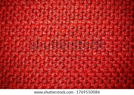 Red structured textile background with vignetting, blackout at the edges of the photo