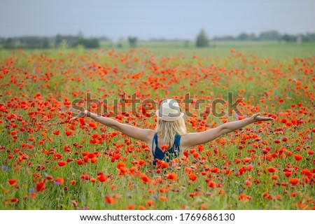 A girl in a poppy field, in a wide landscape. Poppy field to the horizon. Warm tone photography. The picture shows a girl with a summer hat on her head. Poppies in a rapeseed field.