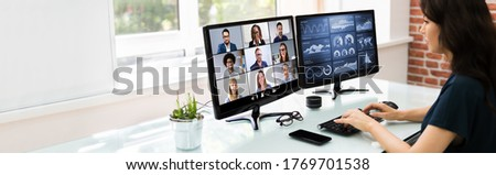 Watching Online Video Conference Meeting In Office Royalty-Free Stock Photo #1769701538
