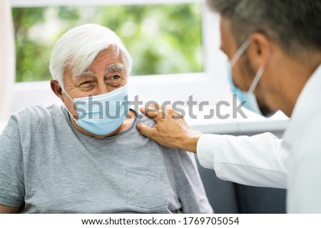 Doctor Talking To Elderly Patient At Home #1769705054