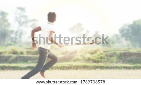 An  Indian or asian young athletic man running for taking a run in the game of cricket. Defocused or blurred image.  #1769706578