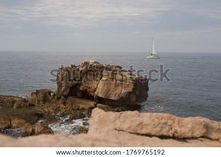 beautiful sailboat in the sea.Beautiful photo of the sea and a sailboat. White sailboat on the background of the sea and rocks. #1769765192