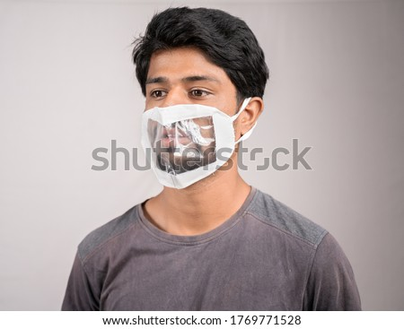 Selective focus on eyes, young man with transparent Medical face mask, to help hearing impairment or deaf people to understand lipreading during coronavirus or covid-19 outbreak Royalty-Free Stock Photo #1769771528