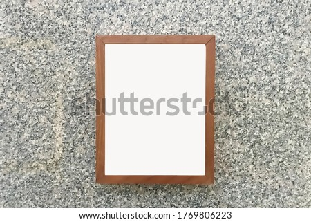 Wooden picture frame hangging on granite glitter wall