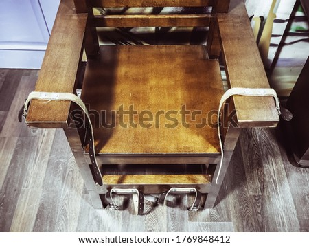 Old wooden chair with shabby leather straps attached to the armrests and legs. Chair for torture. Antique electric chair. Museum exhibit. Noise, film grain #1769848412