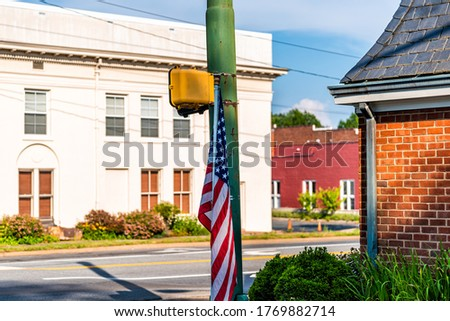 Orange, Virginia historic downtown town city in countryside with brick buildings on street and american flag at pedestrian crossing light #1769882714
