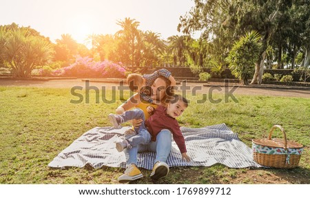 Young mother having fun in a park with her twin sons - Young family with a pic nic and having playful time together - Family, single mother and children love concept