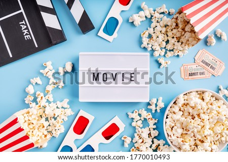 Lightbox with the word Movie, popcorn, 3d glasses and movie tickets top view flat lay on blue solid background