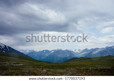 Beautiful view from mountain pass to great snowy mountains under cloudy sky. Dramatic alpine landscape with snow mountains in rainy weather. Gloomy scenery with giant mountain ridge in overcast day. Royalty-Free Stock Photo #1770037193