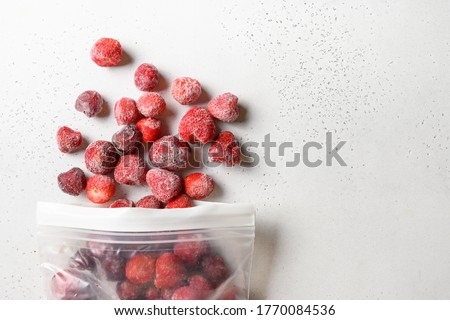 Frozen strawberries in plastic packet on white background. View from above. Stocks. Copy space. Healthy eating. Vitamins. Vegetarian, vegan food.